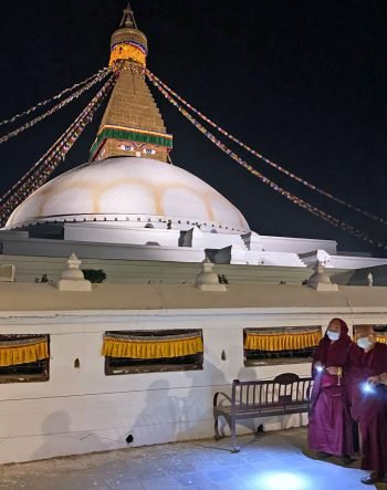 Lama Zopa Rinpoche and attendants circumambulating Boudha Stupa with flashlights