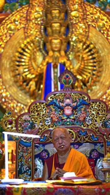 Lama Zopa Rinpoche on teaching throne withgolden 1000-Armed Chenrezig statue behind him