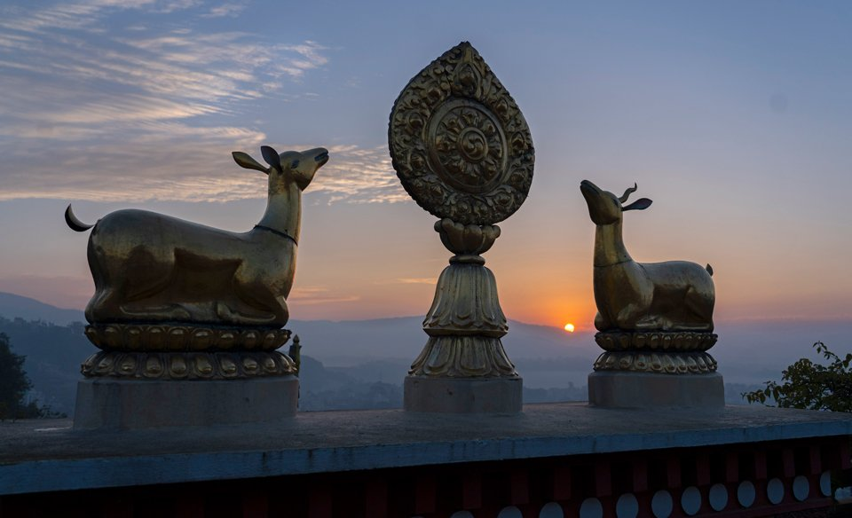 Kopan Monastery's deer and dharmachakra with sunrise behind them