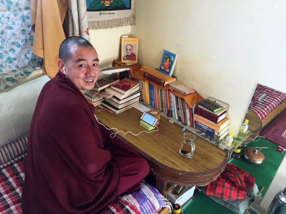 Tibetan Buddhist monk seated at a low table and wearing headphones connected to a smart phone propped up on the table.