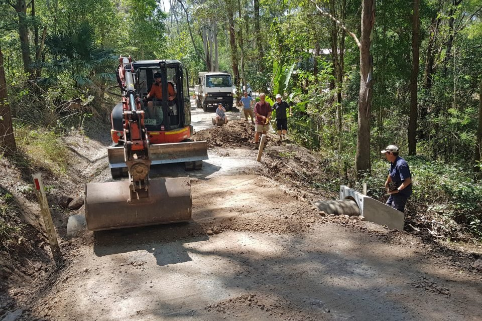 Trucks and crew doing road work in a forested area.