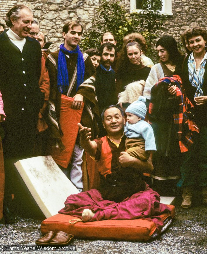 Lama Yeshe sitting on a cushion, holding a baby, surrounded by students in front of an old stone building
