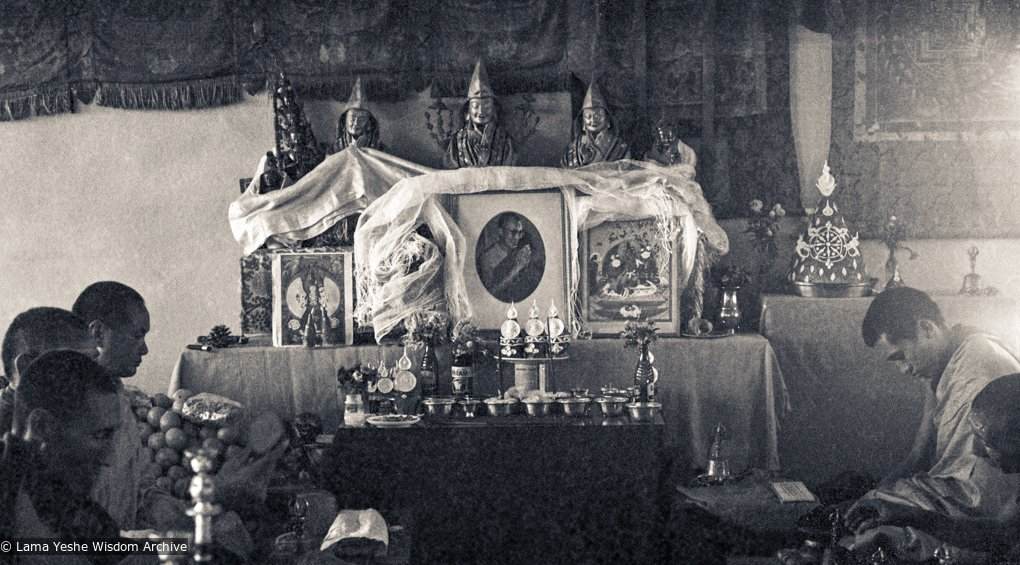 black and white photo of Lama Yeshe and Lama Zopa Rinpoche doing prayers in front of a altar with a photo of HH Dalai Lama on it