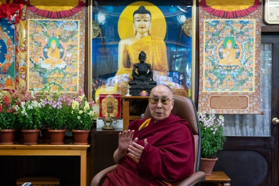HH Dalai Lama addressing the camera with flowers, thangkas, and statues behind him