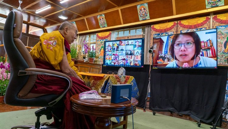 His Holiness the Dalai Lama listening to a question from a woman on a screen