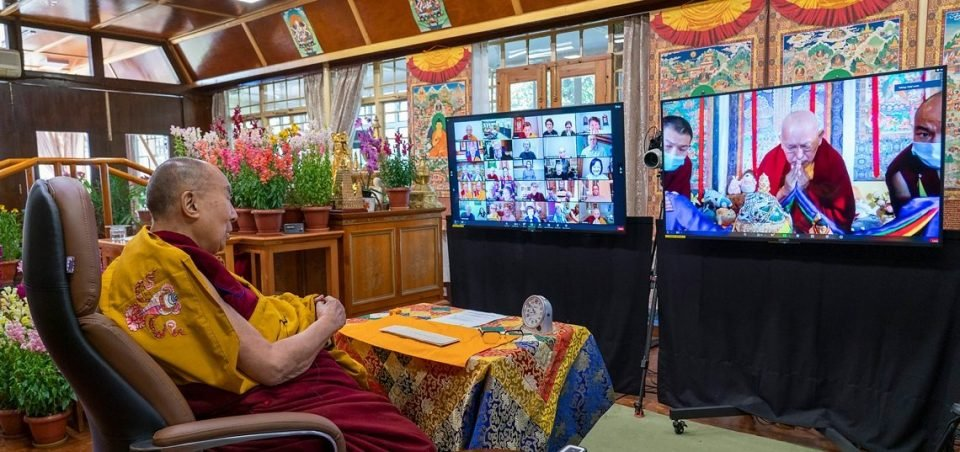 His Holiness the Dalai Lama watching a video screen of Lama Zopa Rinpoche offering a mandala