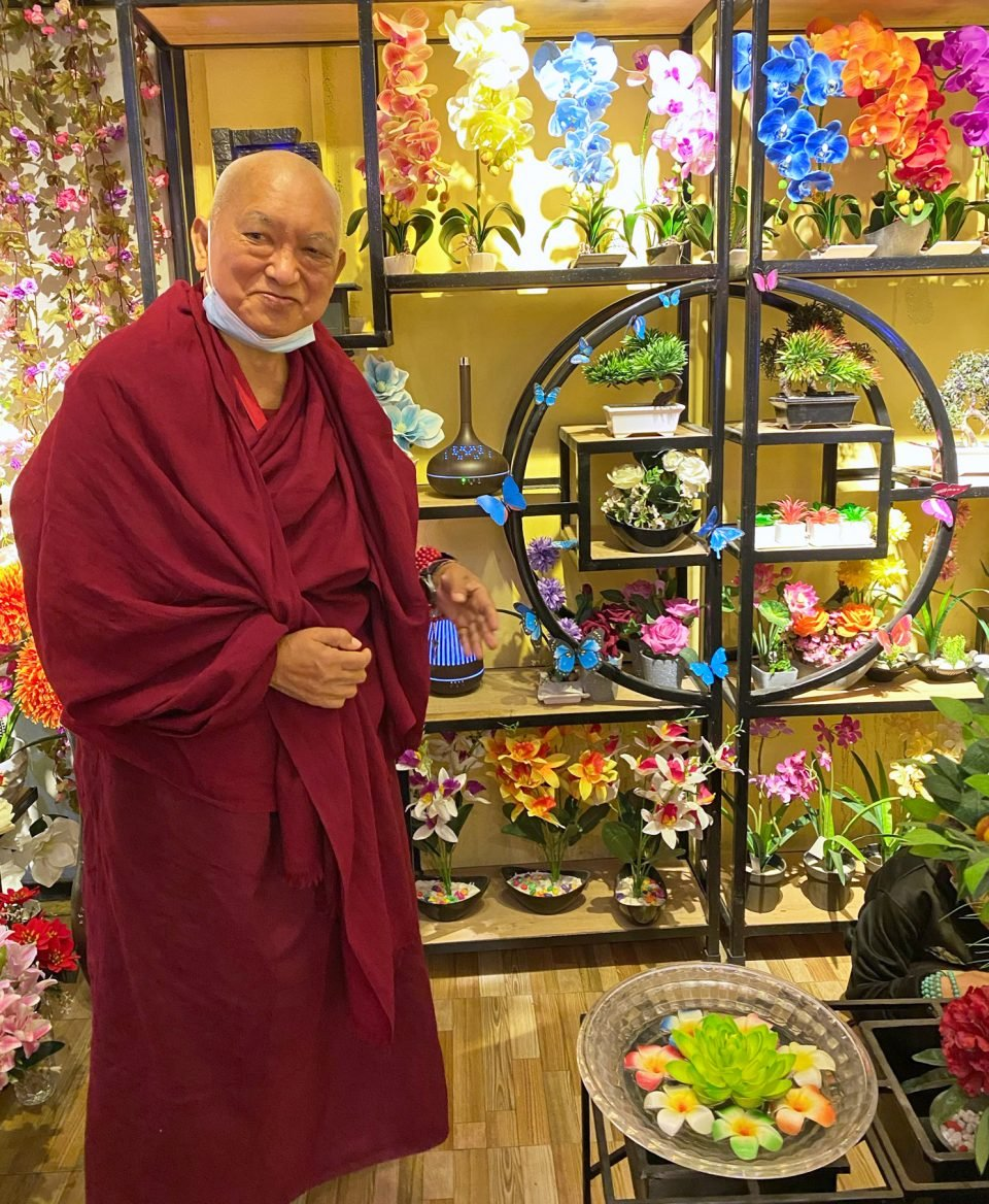 Lama Zopa Rinpoche smiling while standing next to flowers on shelves