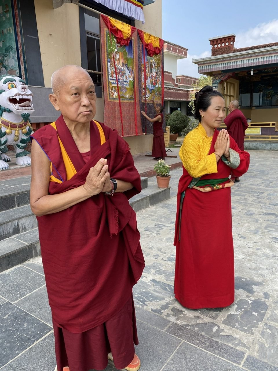 Lama Zopa Rinpoche and Kharo-la standing in front of large Tara thangkas with hands in prayer mudra.