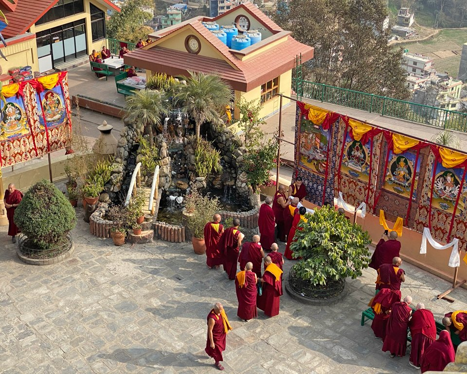 Looking down on the Kopan Gompa courtyard where many thangkas are hung and Rinpoche is viewing them with other monks and nuns
