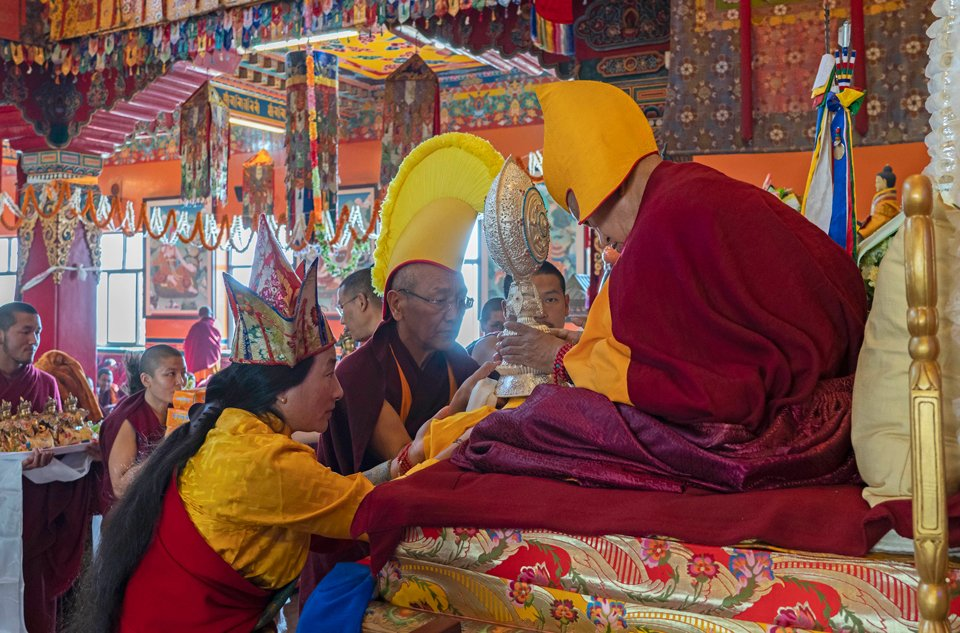 Khadro-la and Khen Rinpoche Geshe Chonyi offering a dharmachakra to Lama Zopa Rinpoche, who is seated on a throne, wearing golden hat