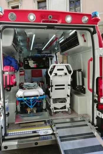 Looking inside of an ambulance from the back door with two stretchers and medical equipment stored.