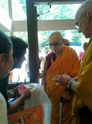 Two people holding khatas and leaning forward in line to greet Rinpoche as he walks towards them.