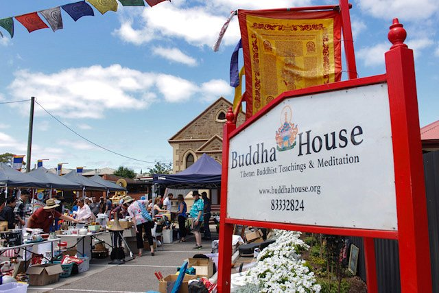 Buddha house billboard style sign welcomes visitors to the center on a sunny blue sky day with people browsing items on tables in the yard.