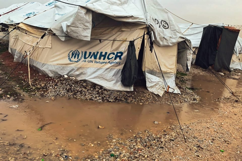 Big tent leaning over under weight of plastic sheeting roof labeled UNHCR standing in a rocky and muddy place.