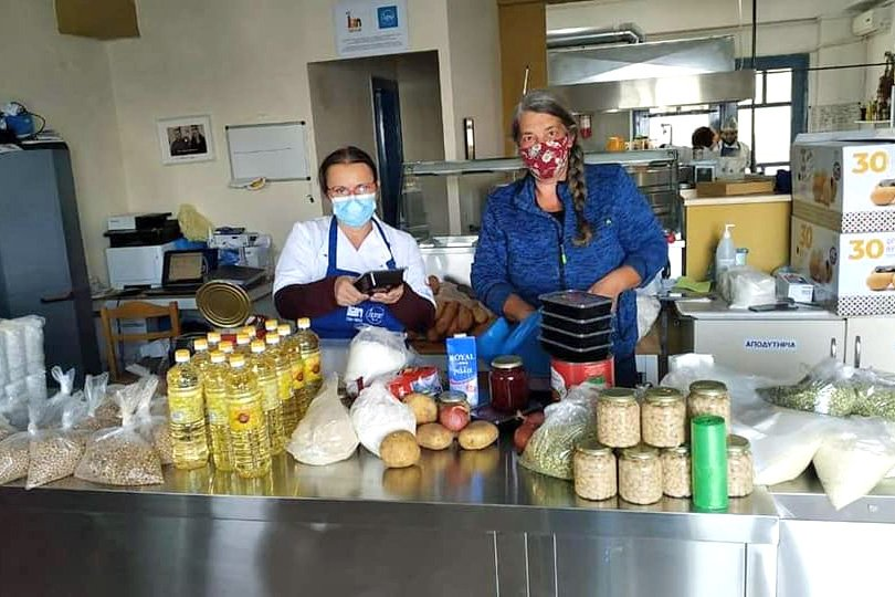 Two people wearing face masks standing in a kitchen in front of a counter stacked with vegetables grains and other cooking supplies.