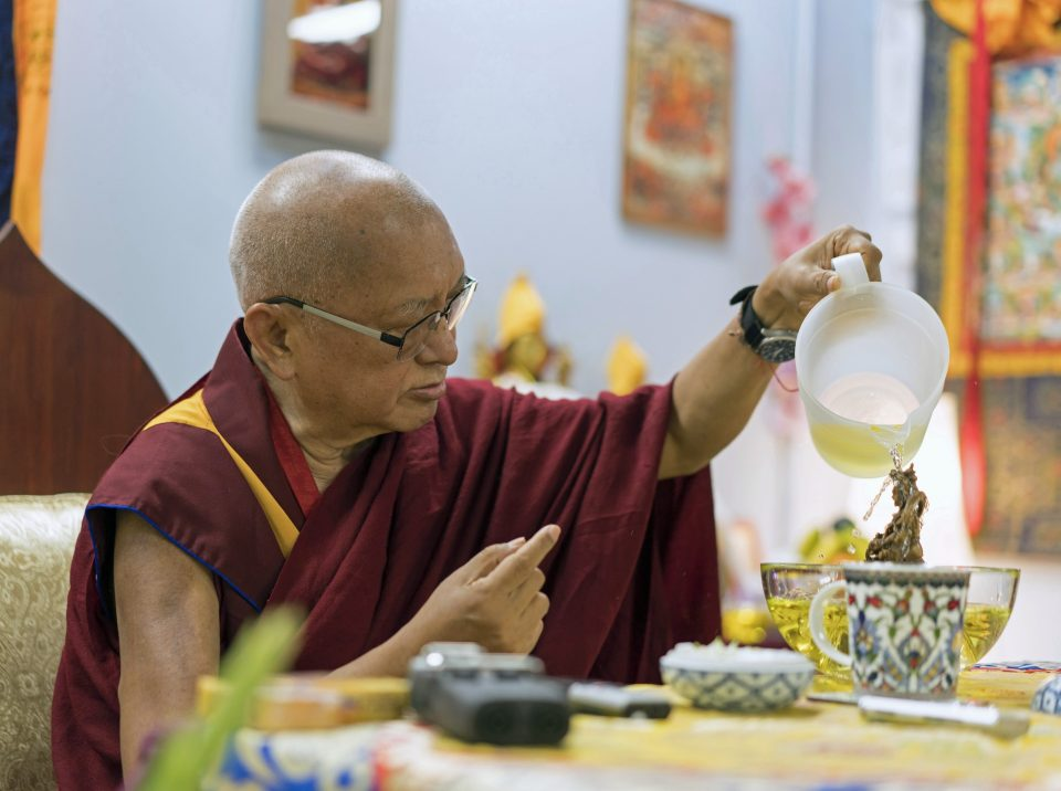 Lama Zopa Rinpoche seated in front of a table pouring water over a statue inside of a bowl.