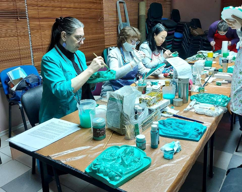 A small group of people seated around a table covered in paints and plaster tsa-tsas intently painting tsa-tsas with green paint.