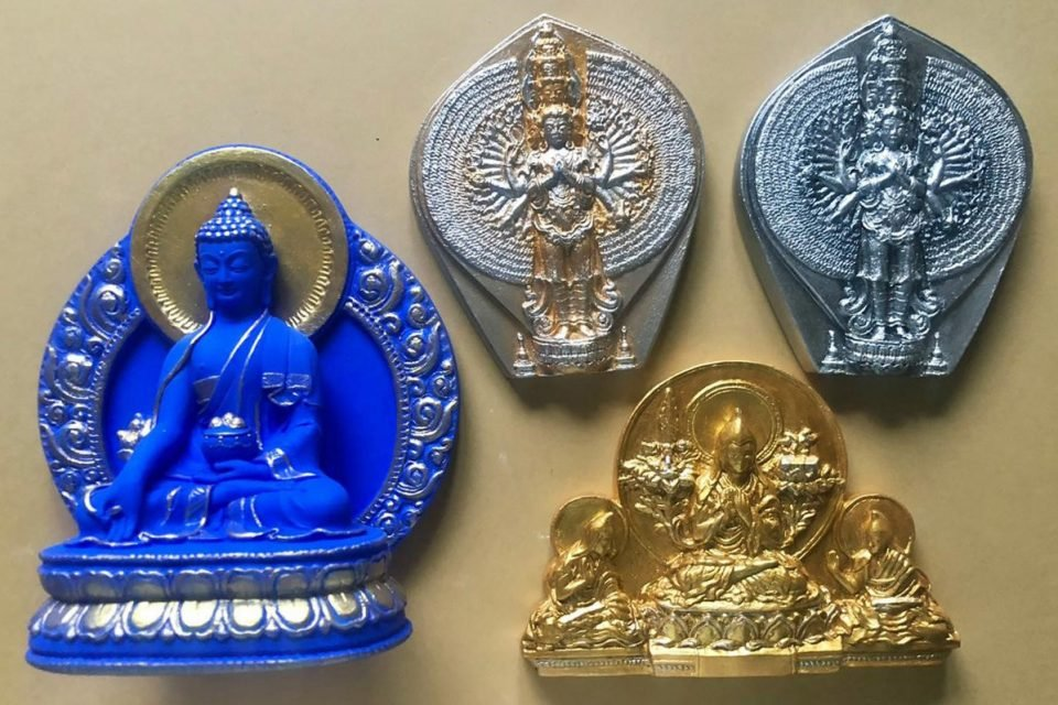 Four painted tsas tsas made from plaster in blue, silver, grey, and gold.