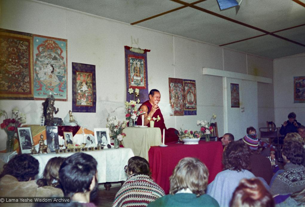Lama Yeshe seated in front of a thangka, giving a teaching to a group of students