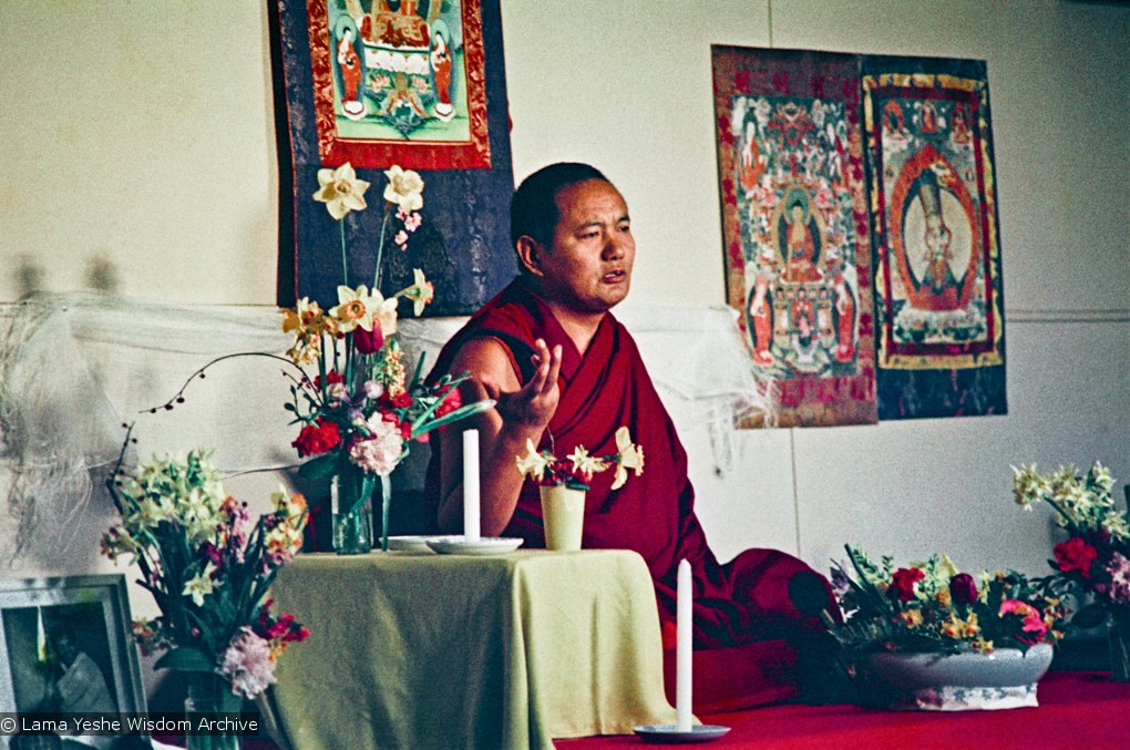 Lama Yeshe seated in front of a thangka, giving a teaching