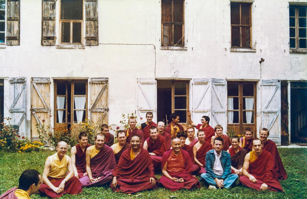 Archive photo of Western Sangha sitting with Lama Yeshe in front of a white building
