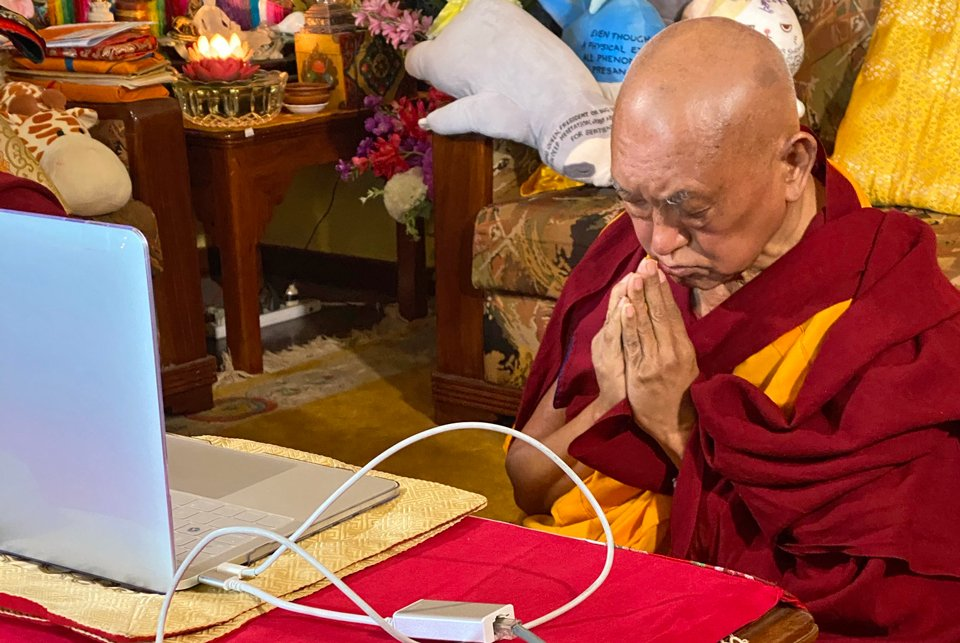 Lama Zopa Rinpoche sitting in front of a computer with his hands in prostration mudra