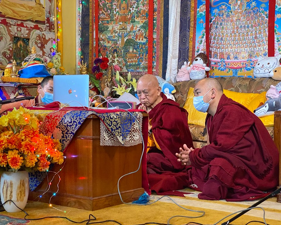 Lama Zopa Rinpoche and two attendants sit on the floor in front of a computer watching