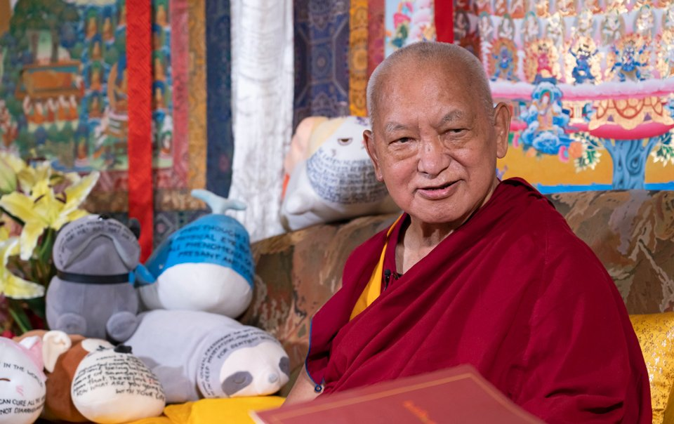 lama zopa rinpoche sitting on a couch with many stuffed toys