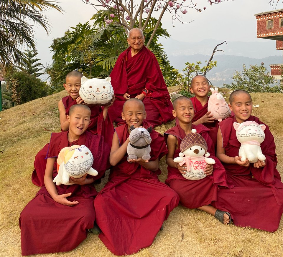 smiling young monks holding up stuffed toys in front of Lama Zopa Rinpoche seated under a blooming tree
