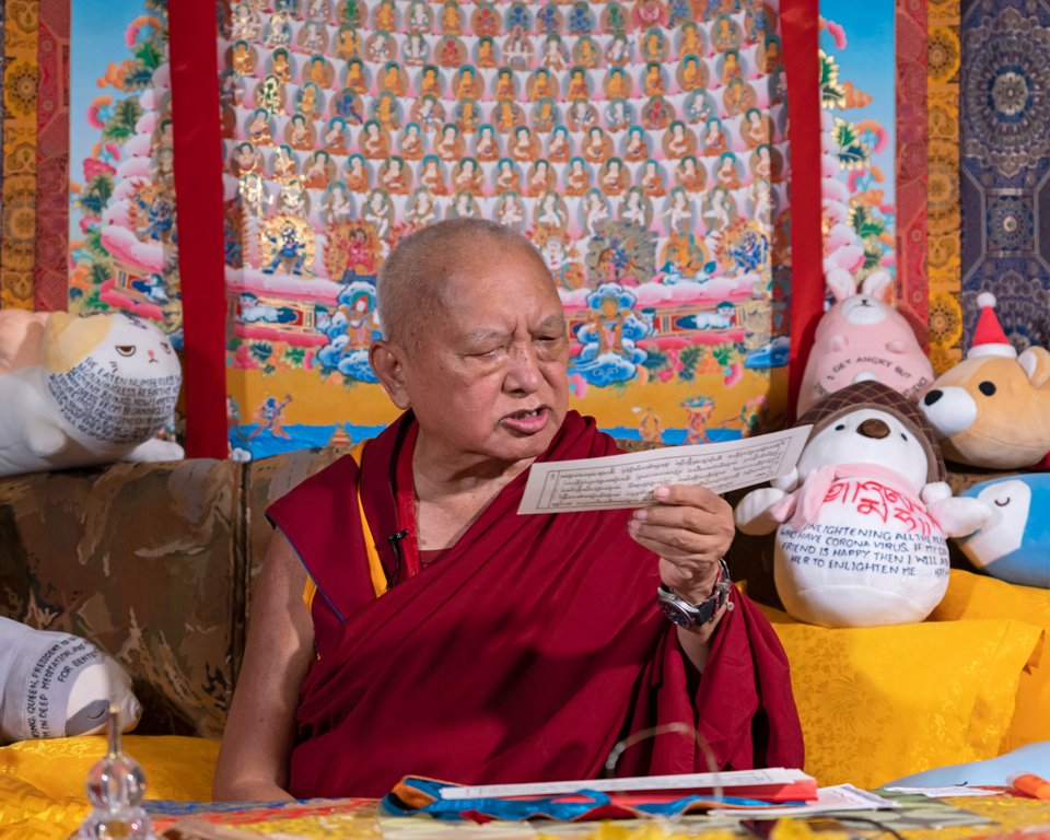 Lama Zopa Rinpoche reading a pecha page while seated on a couch in front of a large thangkha of the merit field