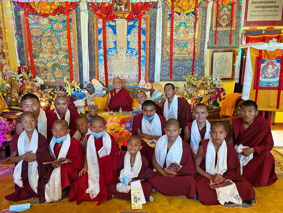 Lama Zopa Rinpoche seated on a couch with many monks, some very young, kneeling in front of him