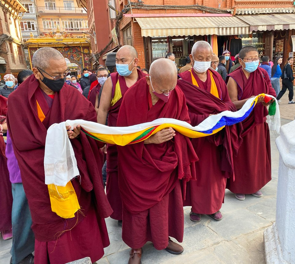 Four robed monastics wearing maskes hold five colored khatas as offering