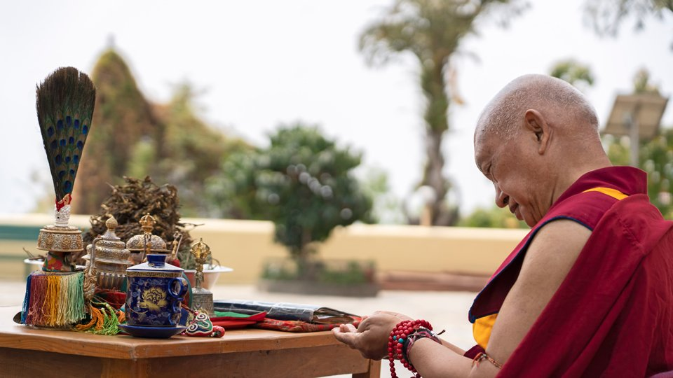 profile view of Rinpoche with puja implements seated outside
