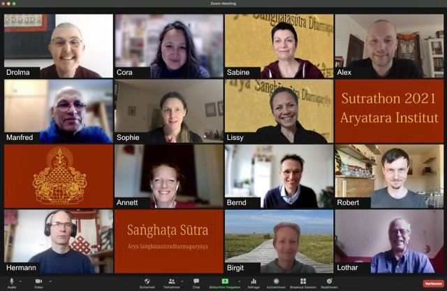 Thirteen smiling people gathered on Zoom.
