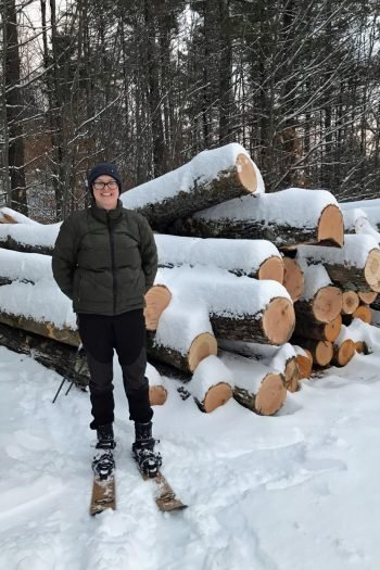 Dawn wearing a warm winter jacket and hat standing on skis in front of a pile of large cut logs covered in snow.