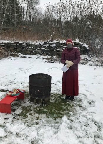 Nun standing next to a black metal garbage can with a low table covered in red cloth and a tray of ritual items on the ground covered in snow.