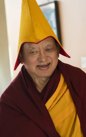 Lama Zopa Rinpoche smiling with a puja hat on