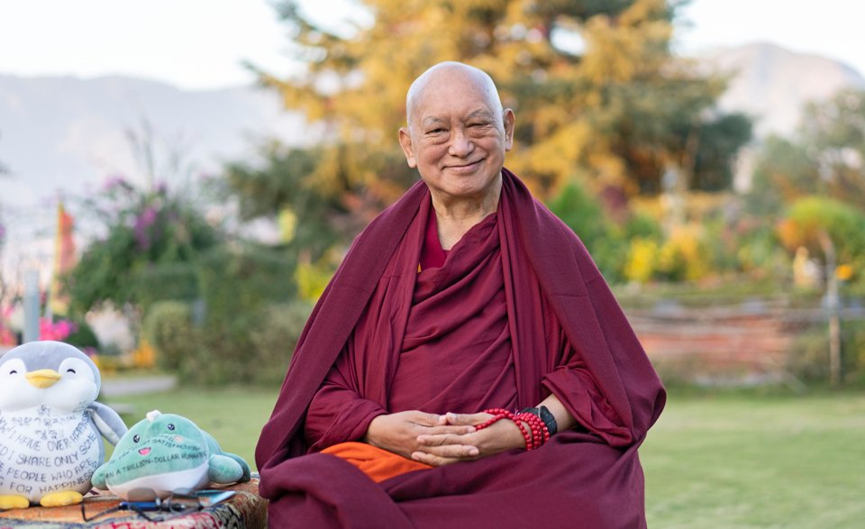 Lama Zopa Rinpoche seated in a garden next to stuffed toys with Dharma messages written on them