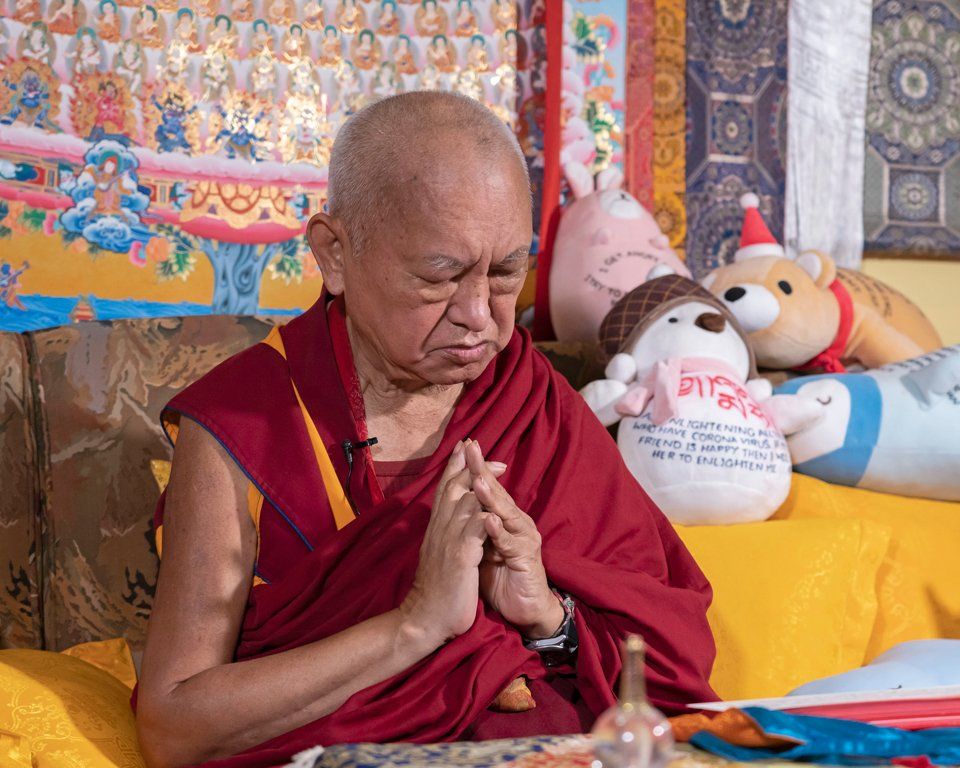 Lama Zopa Rinpoche seated on a golden couch with hands together in prayer