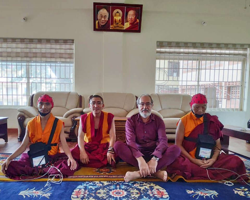 Three Tibetan monks and one Western scientist seated together