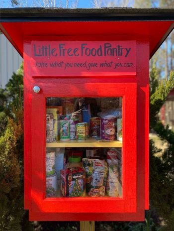 Red cabinet with glass front window on a pole and assorted canned and boxed food items inside.