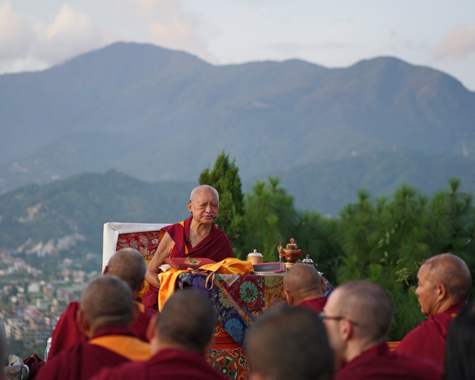 Lama Zopa Rinpoche seated on a throne teaching gathered monks outside, with buildings and mountains in the background