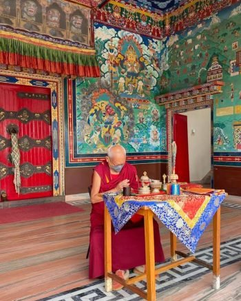 Lama Zopa Rinpoche wearing a mask doing puja by himself