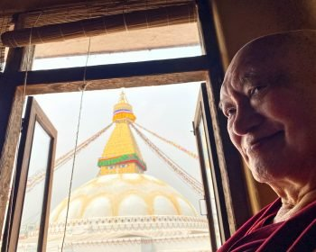 Rinpoche smiling in front of a window overlooking Boudha Stupa