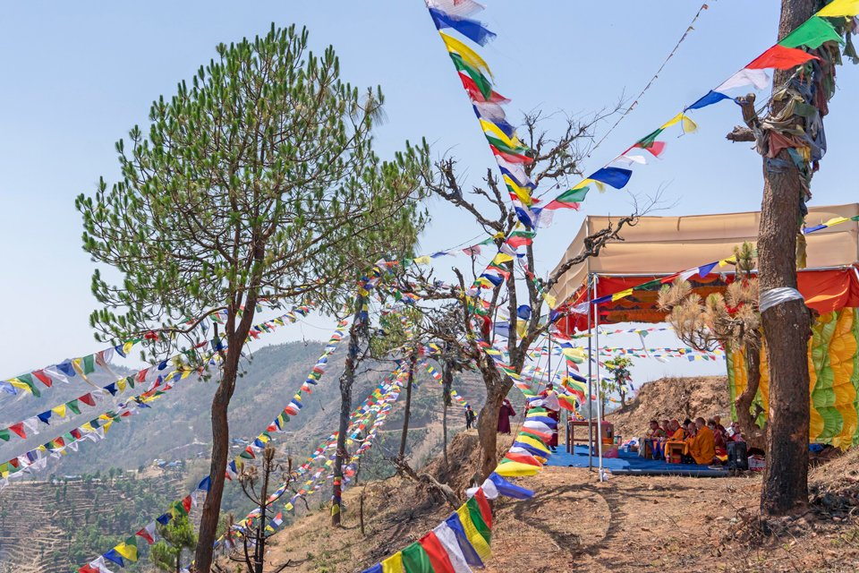 Prayers flags and a view of foothills and terraced land in the distance and an open tent with people doing prayers