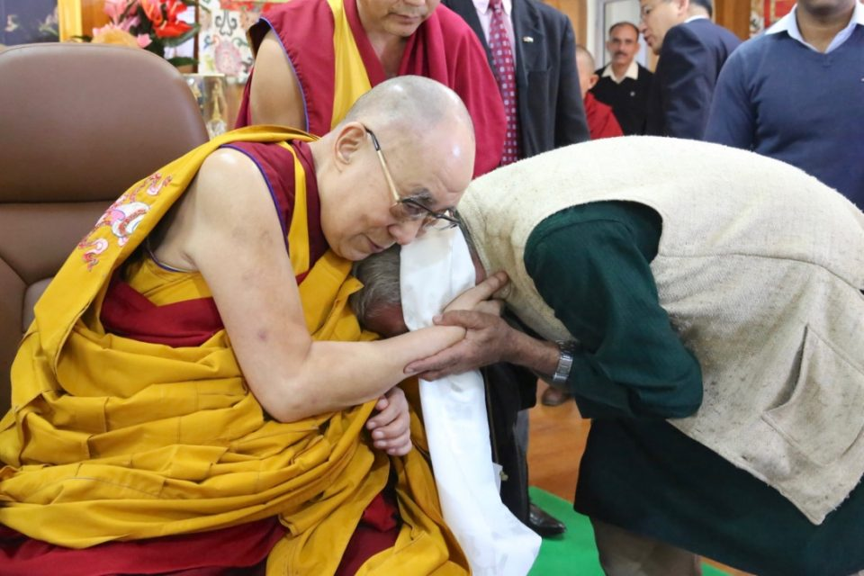 The Dalai Lama resting his head on top of a man's head while the two grasp hands.