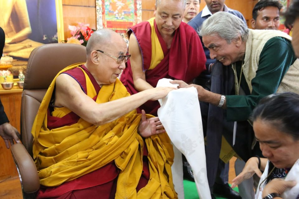 The Dalai Lama accepting a white scarf from a smiling person.