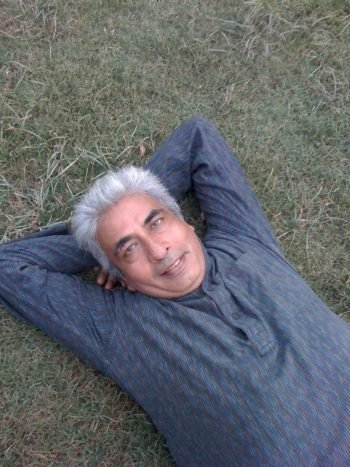 Person relaxing on the grass with arms folded behind the head.