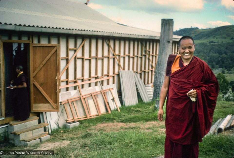 Lama Yeshe smiling standing in front of building and rural hilly landscape
