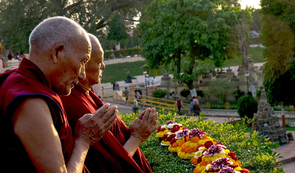 Two monks with their hands folded in prayer with plates of colorful flower offerings in front of them.